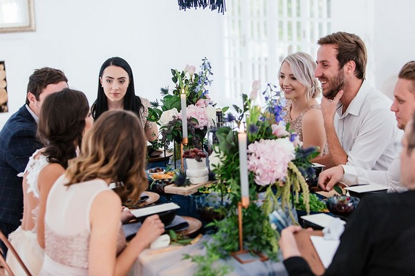 Guests sitting at small table for intimate wedding breakfast