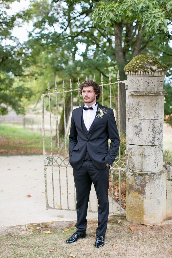 Groom waiting for bride at gates of Chateau de Redon