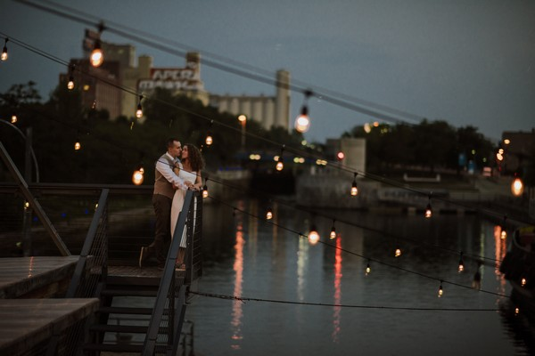 Bride and groom about to kiss on steps by river - Picture by Gabrielle Desmarchais