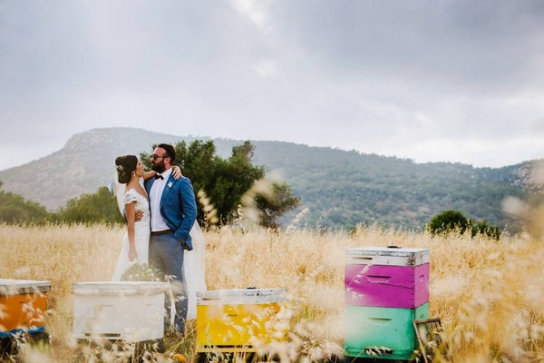 Bride and groom standing in feild next to colourul boxes with hills in the background - Picture by Jonny Barratt Photography