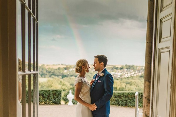 Bride and groom standing in doorway with rainbow in background - Picture by Anna Wood Photography