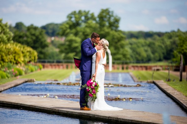 Bride and groom kissing on mbridege over venue water feature - Picture by Joss Denham Photography