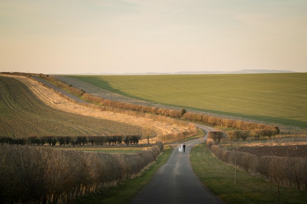 Bride and groom walking down middle of country road - Picture by Linus Moran Photography