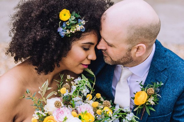 Bride with flowers in her hair sharing intimate moment with groom in blue suit - Picture by Berni Palumbo Photography