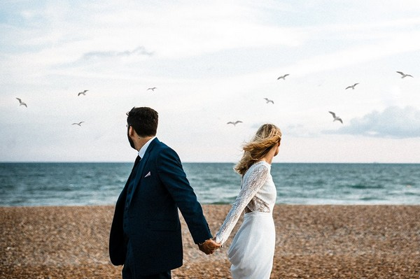 Bride and groom holding hands turning round to see seagulls flying over sea - Picture by Beatrici Photography