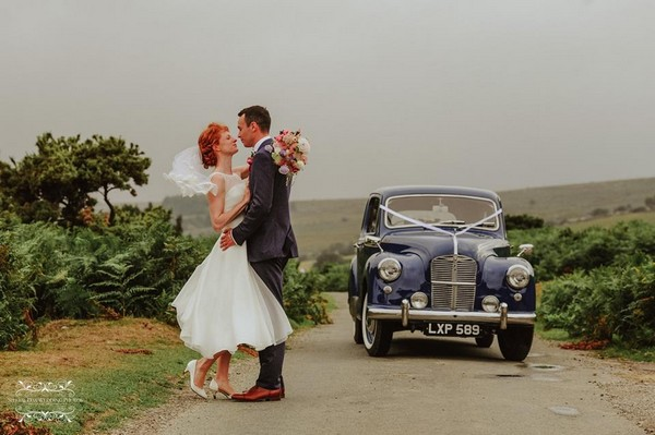 Bride and groom standing in road by classic wedding car - Picture by Special Day Wedding Photos