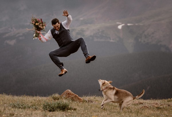 Groom holding bouquet jumping next to dog - Picture by Maddie Mae