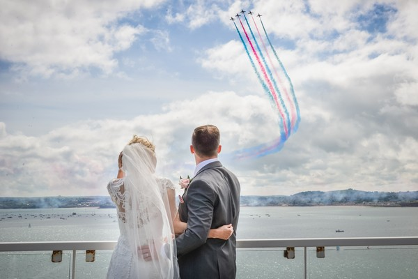 Bride and groom watching as jet planes fly overhead leaving red and blue trails behind them - Picture by Memories and Milestones Photography