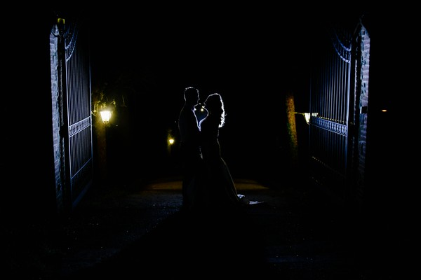Bride and groom at gates of Casa Bruciata at night - Picture by Rebecca Parsons Photography