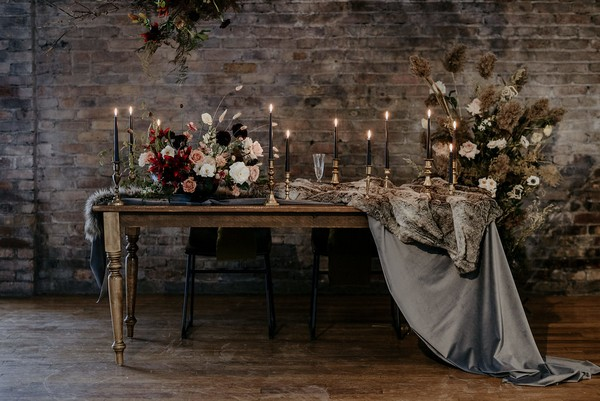 Wedding table with candles, autumnal flower displays and velvet table runner