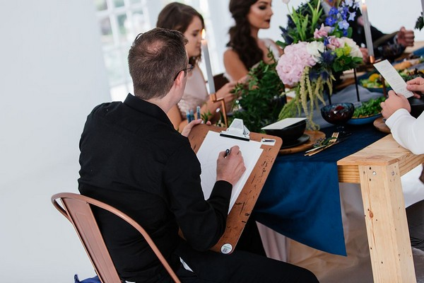 Caricaturist sitting at wedding table drawing guests