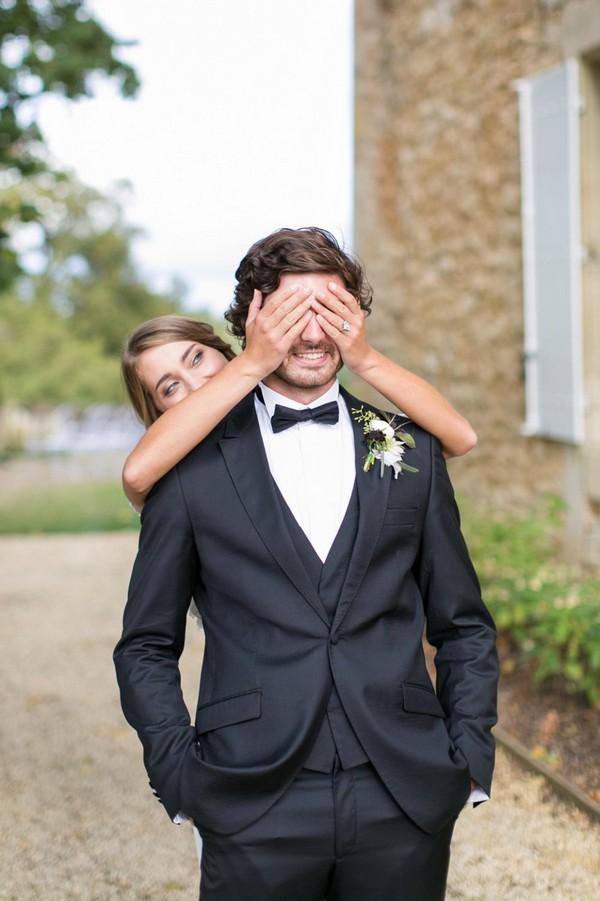 Bride putting hands over groom's eyes