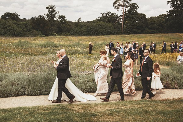 Bride, groom and guests walking down path at Coworth Park