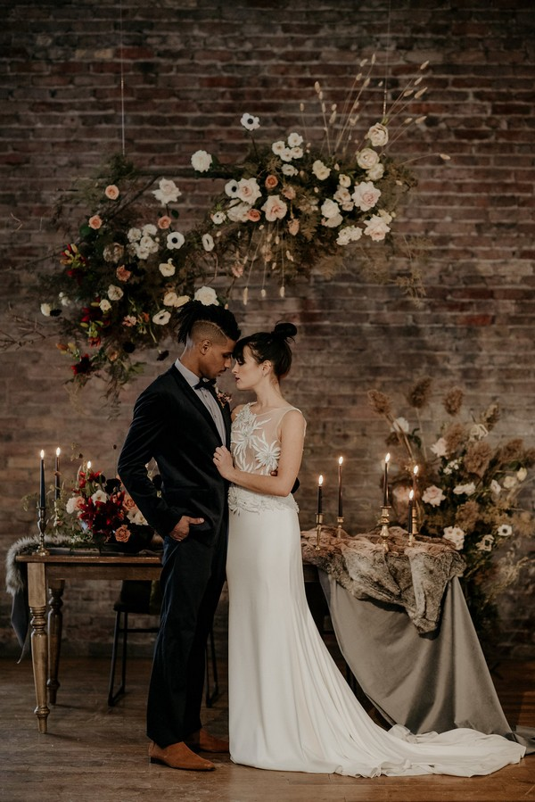 Bride and groom touching heads in front of autumn styled wedding table
