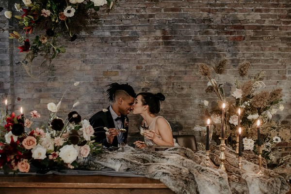 Bride kissing groom on the nose at wedding table