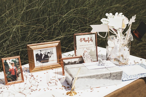 Copper framed pictures on wedding guest book table