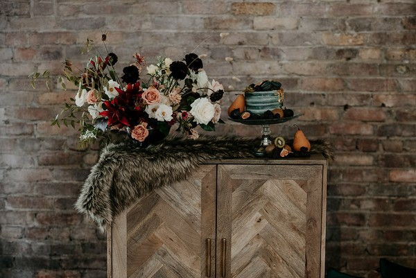 Wedding cake table decorated with fur and autumn flowers