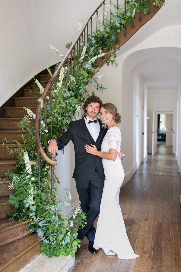 Bride and groom standing by staircase of Chateau de Redon covered in foliage