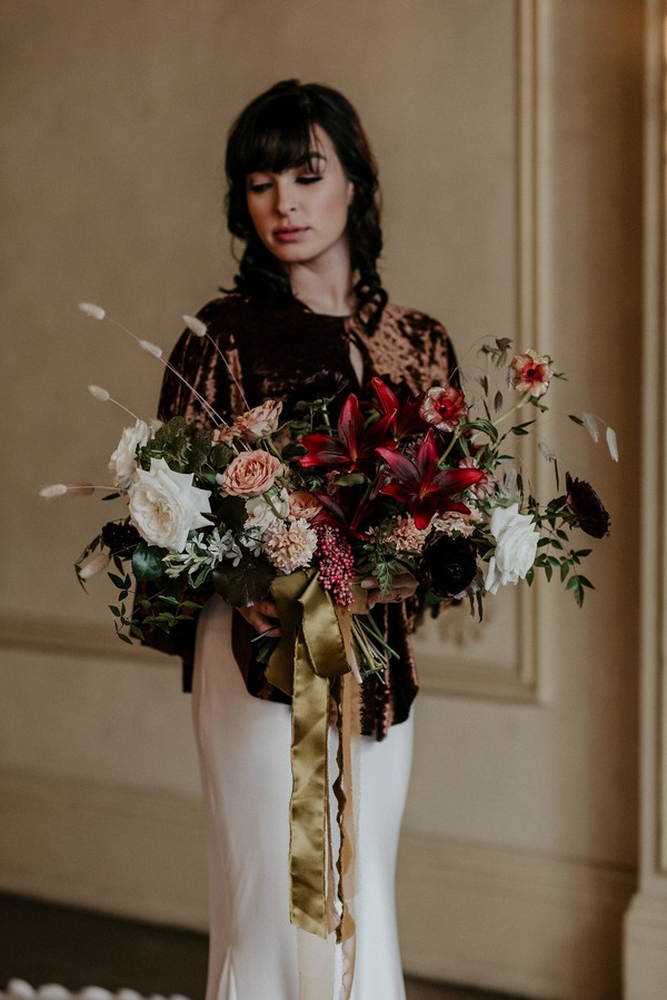 Bride in velvet shrug holding autumnal bouquet