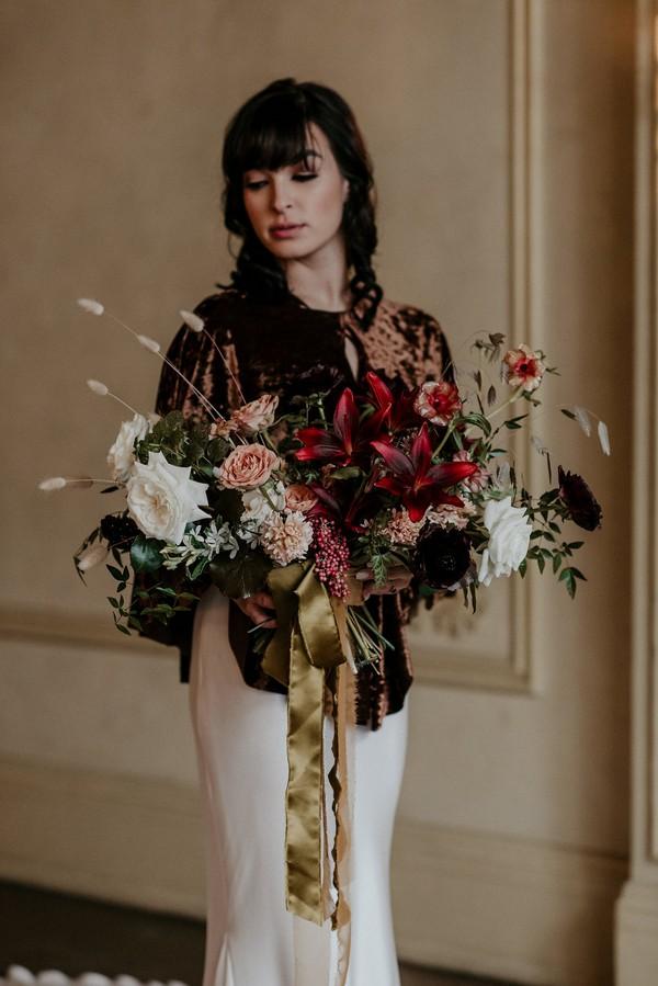 Bride in velvet shrug holding autumnal bouquet