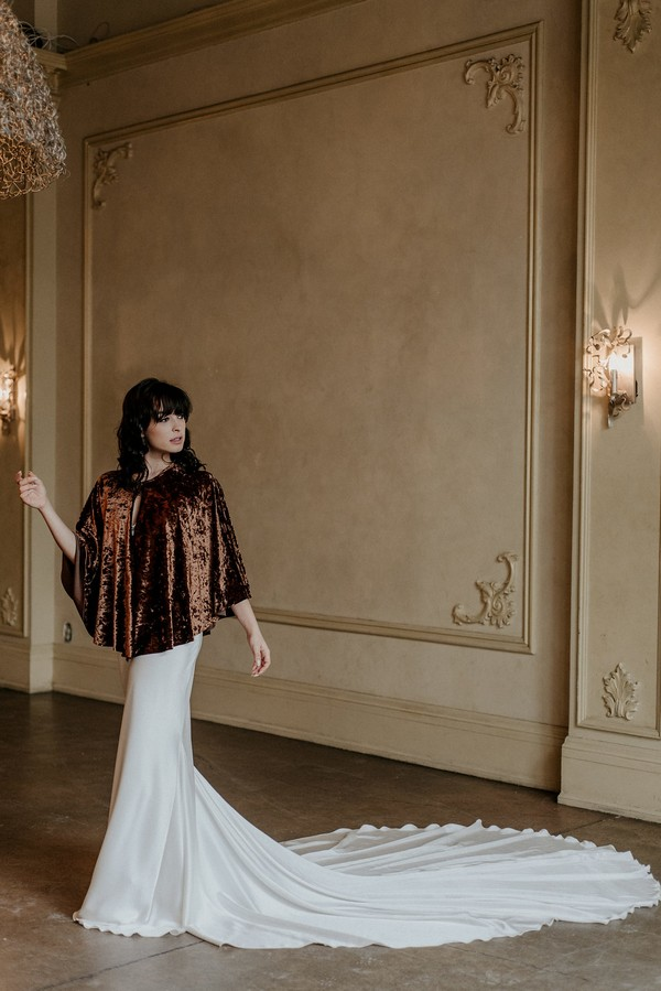 Bride wearing wedding dress with long train and velvet shrug