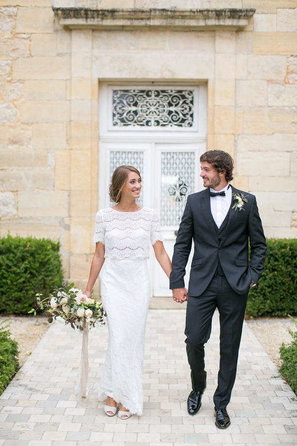 Bride and groom holding hands in front of Chateau de Redon