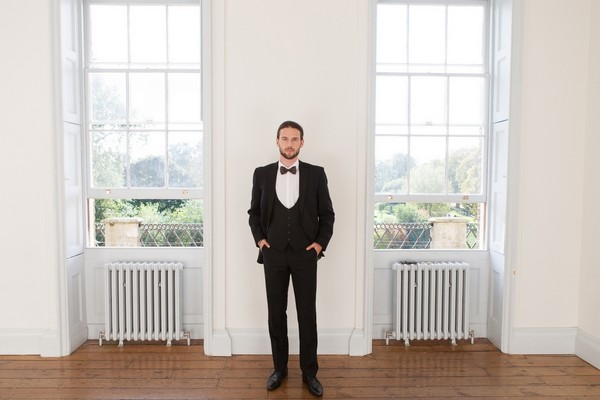 Groom wearing black suit and bow tie in Clissold House
