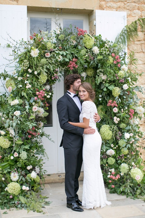 Bride and groom in front of flower and foliage arch