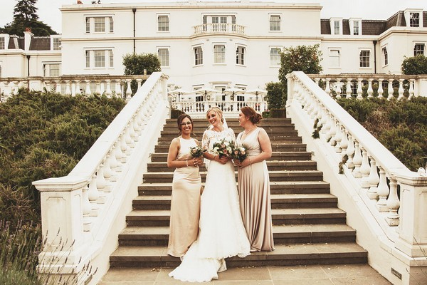 Bride and bridesmaids on steps at Coworth Park