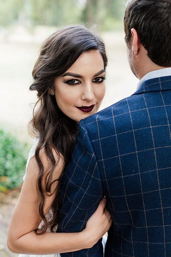 Bride with dark make-up looking over groom's shoulder