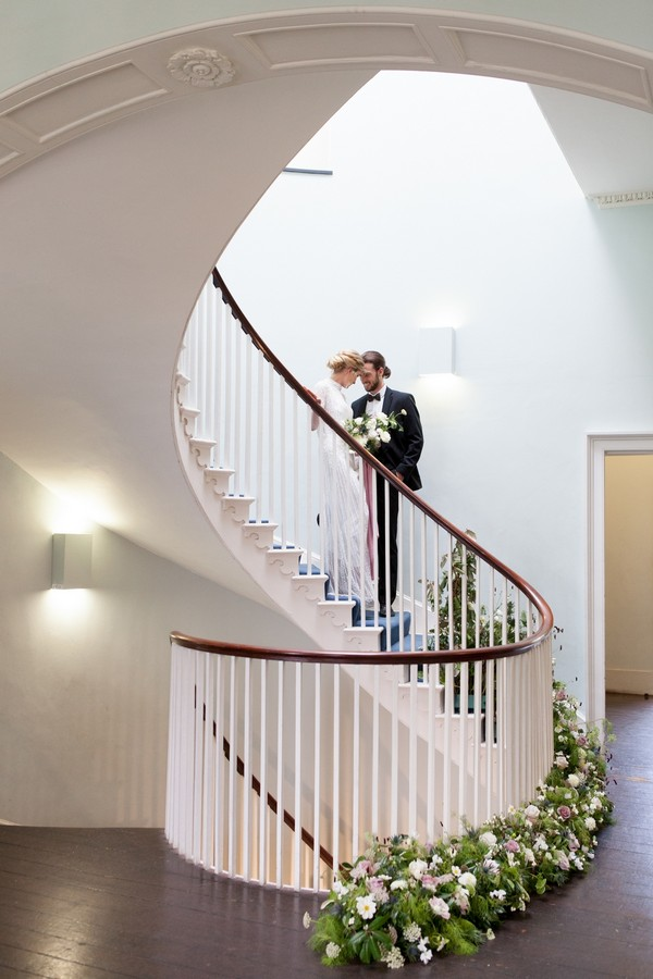 Bride and groom standing on spiral staircase at Clissold House