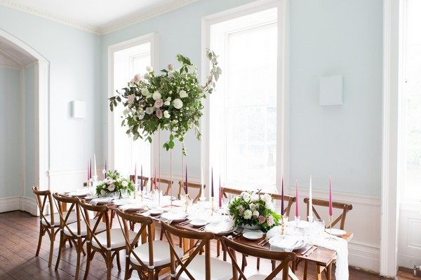 Long wedding table with wooden chairs in dining room at Clissold House