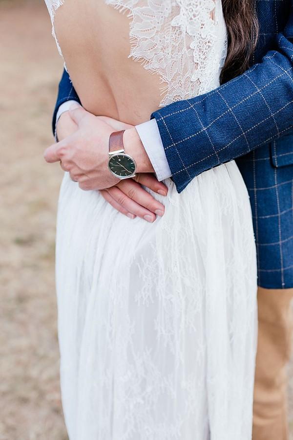 Groom's arms around bride's waist