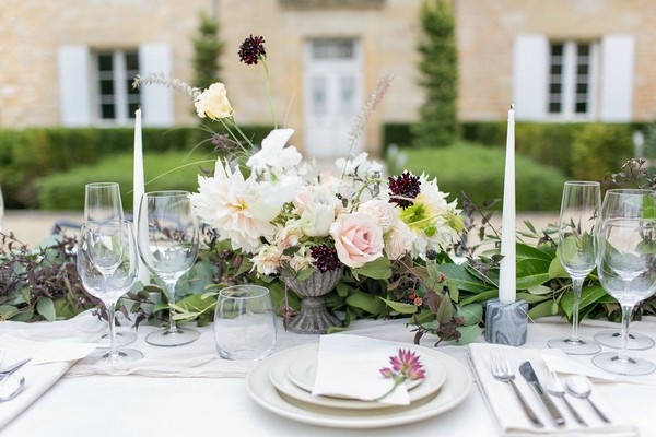 Wedding table flowers in front of place setting