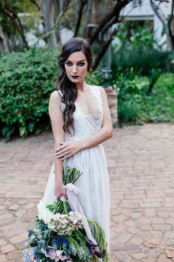 Bride with dark make-up holding large winter wedding bouquet