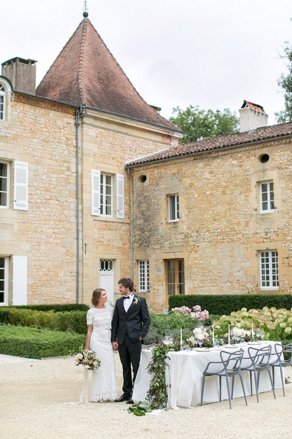 Bride and groom standing by wedding table outside Chateau de Redon