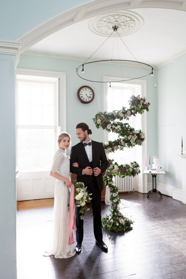 Bride and groom standing by spiral floral arrangement in Clissold House
