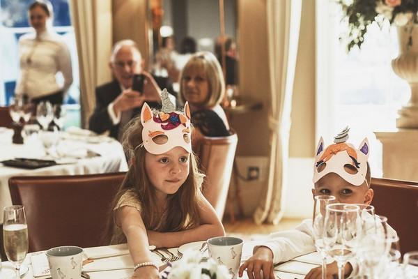 Children wearing masks at wedding table