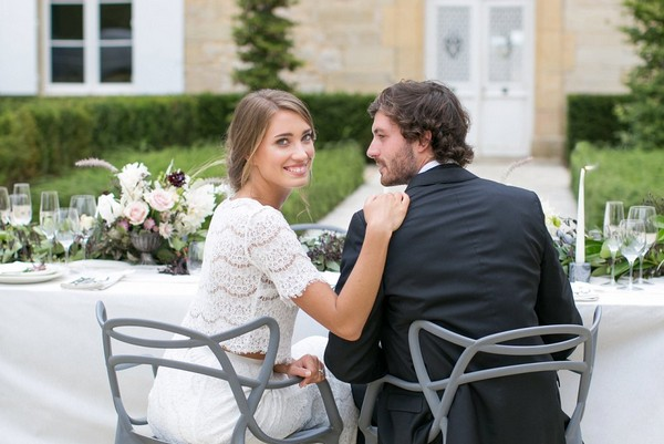 Bride with hand on groom;s shoulder at wedding table