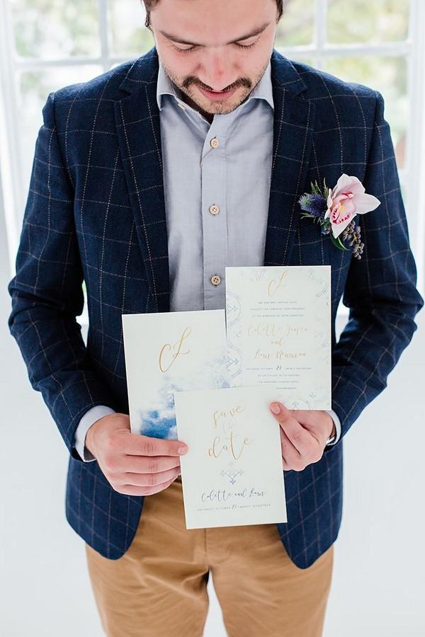 Groom holding wedding stationery
