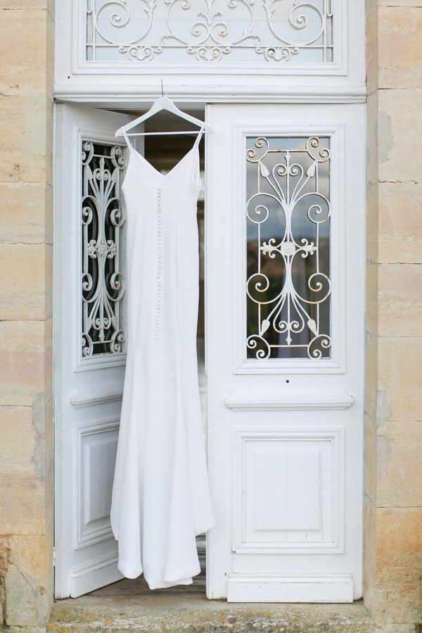 Wedding dress hanging in doorway at Chateau de Redon