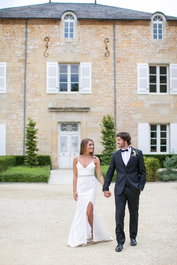 Bride and groom walking in front of Chateau de Redon