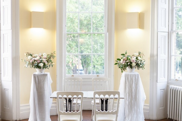 Chairs and floral arrangements at front of wedding ceremony room at Clissold House