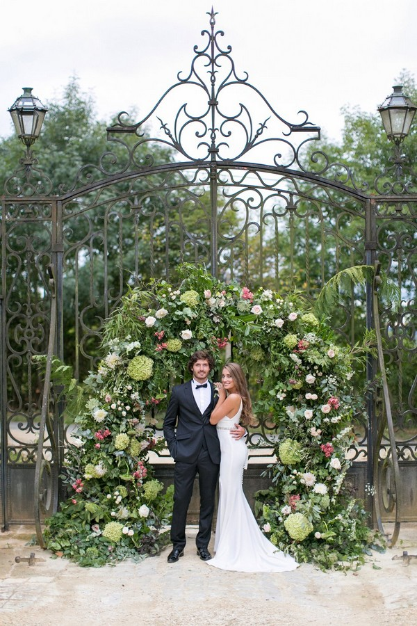 Bride and groom in front of large flower and foliage arch on gates of Chateau de Redon