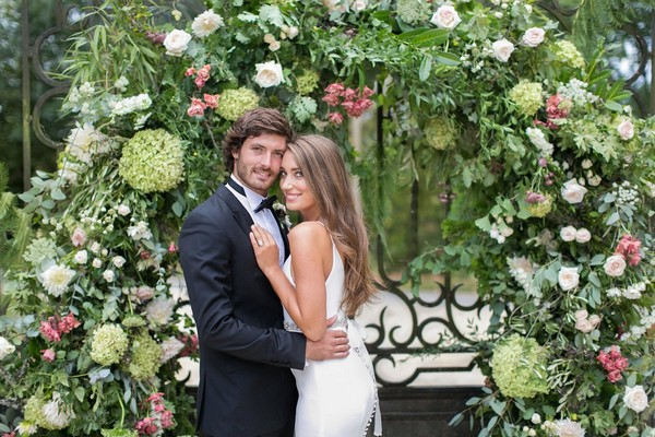 Bride and groom in front of large flower and foliage arch
