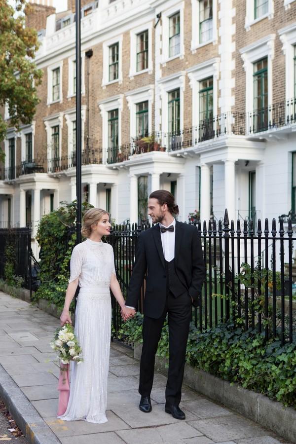 Bride and groom walking past railings