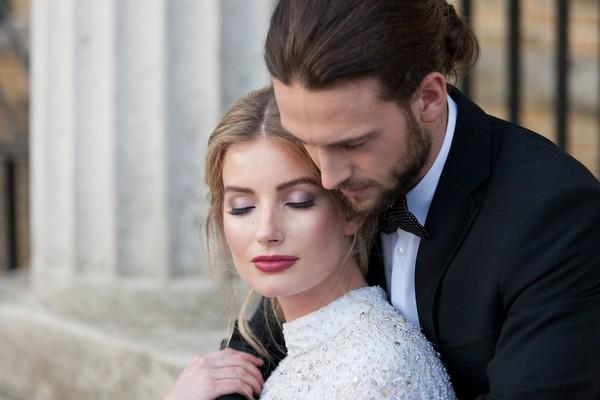 Bride with eyes shut as groom hugs her from behind