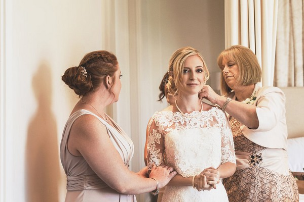 Bride getting ready for wedding with mother and bridesmaids