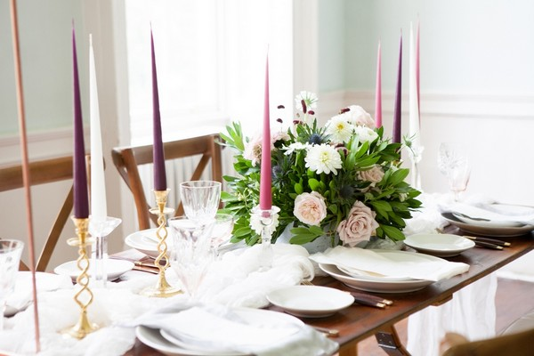 Coloured candles and flowers on wedding table