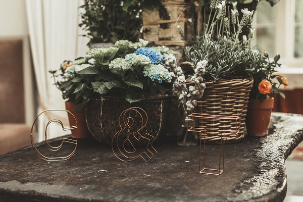 Table with baskets of wedding flowers and copper wire letters